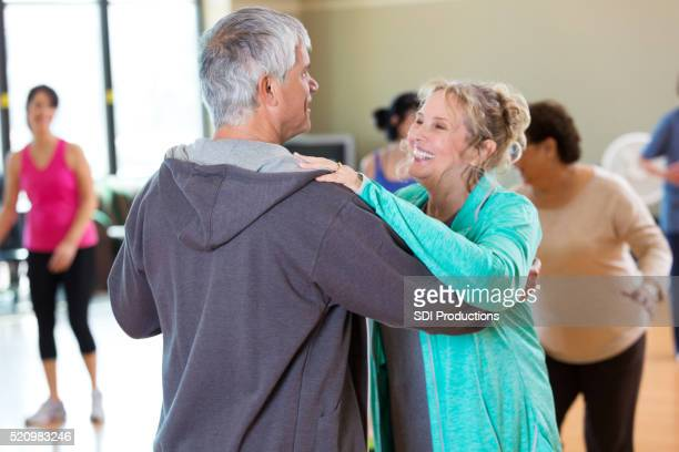Happy senior couple take ballroom dancing lessons