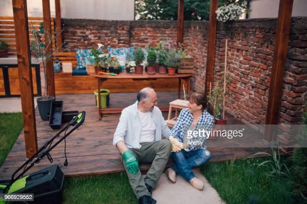 Happy senior couple taking a break from repotting plants