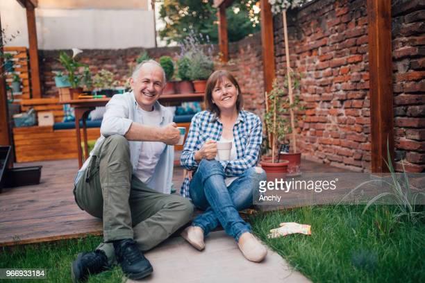 Happy senior couple taking break in the garden from re-potting plants