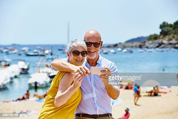 Happy senior couple taking selfie on beach