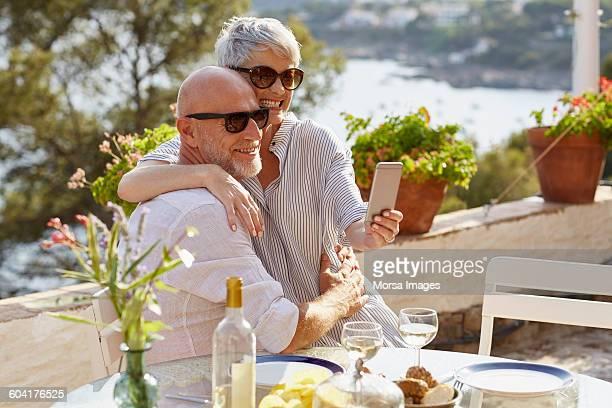 Happy senior couple taking selfie through phone