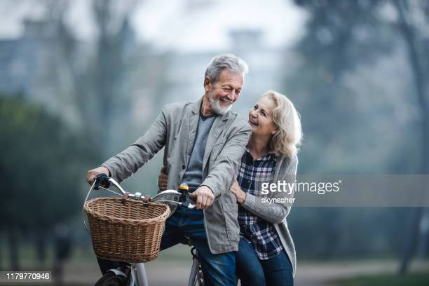 happy senior couple talking while cycling in nature. - mature couple stock pictures, royalty-free photos & images