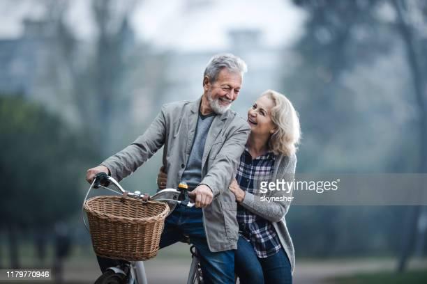自然の中でサイクリングしながら話す幸せなシニアカップル。 - 熟年カップル ストックフォトと画像
