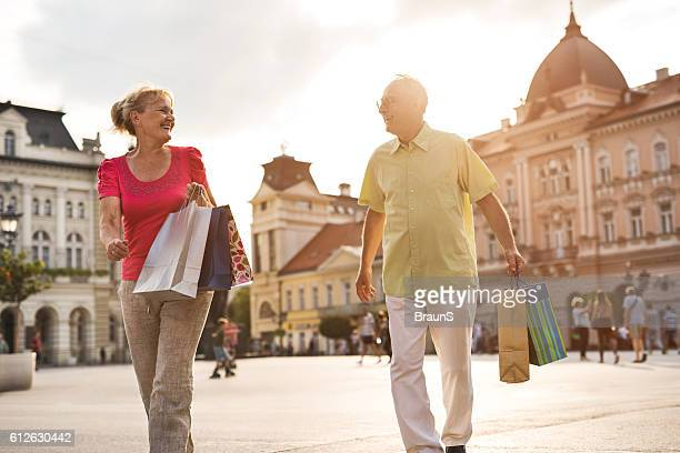 happy senior couple talking while shopping in the city. - commercial activity stock pictures, royalty-free photos & images