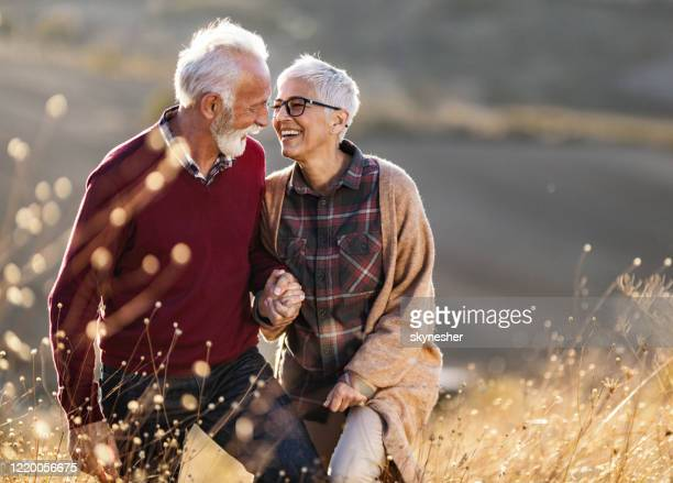 happy senior couple talking while walking on a hill in autumn day. - senior couple stock pictures, royalty-free photos & images