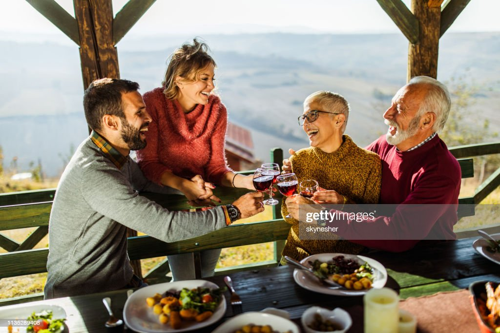 Happy senior couple toasting with young couple during lunch on a terrace. : Stock Photo