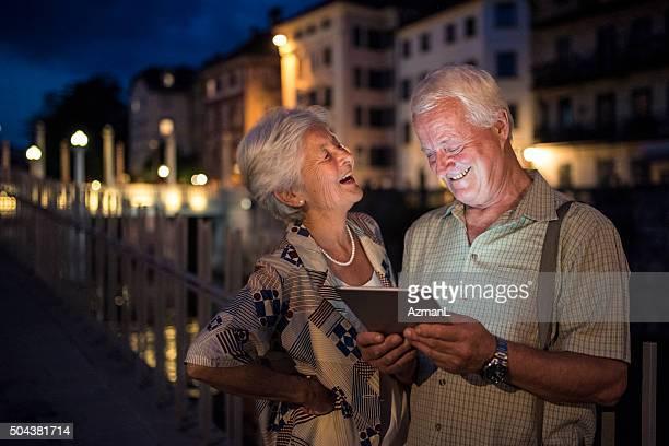 Glücklich altes Paar mit tablet PC in der Nacht