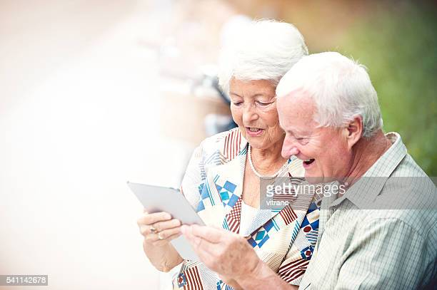 Happy senior couple using digital tablet in park
