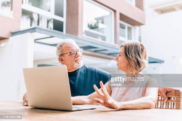 happy senior couple using laptop at home - grounds stock pictures, royalty-free photos & images