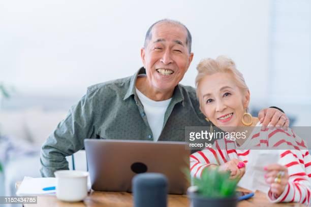 自宅でノートパソコンを使用して幸せな先輩カップル - 気が若い ストックフォトと画像