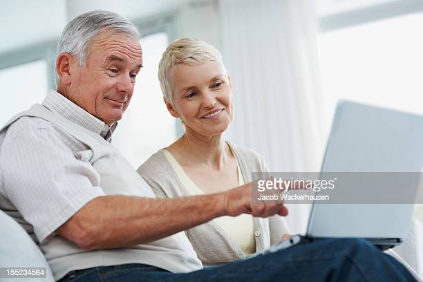 Happy senior couple using laptop at home