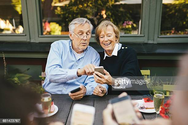 Happy senior couple using mobile phone at outdoor restaurant