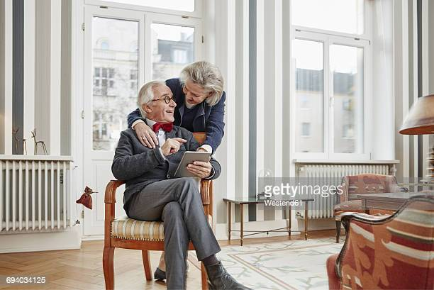 Happy senior couple using tablet at home