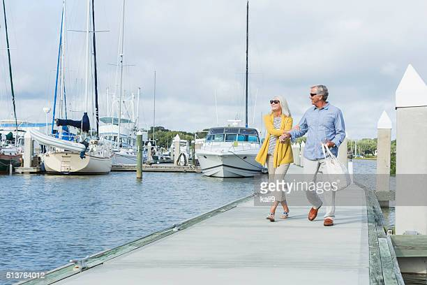 happy senior couple walking along harbor holding hands - pir bildbanksfoton och bilder