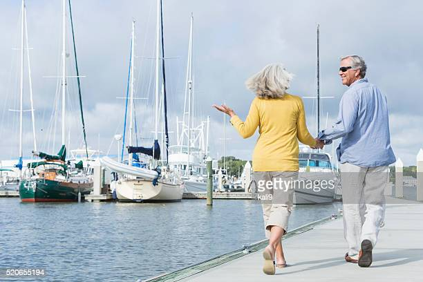 Happy senior couple walking along harbor holding hands
