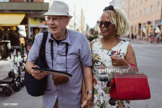 happy senior couple walking in city - clutch bag stock pictures, royalty-free photos & images