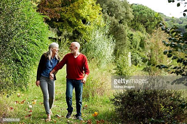 happy senior couple walking in park - 55 59 jaar stockfoto's en -beelden