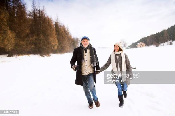 Happy senior couple walking in snow-covered landscape