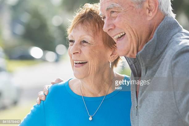 Happy senior couple watching something and smiling