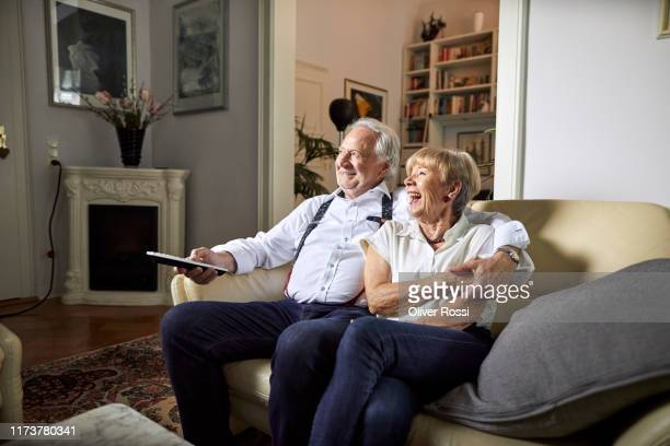 happy senior couple watching tv at home - retirement stock pictures, royalty-free photos & images