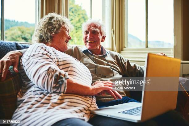 happy senior couple with a laptop at home