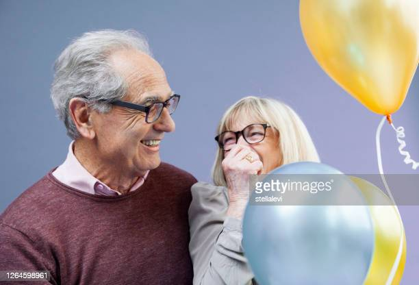 happy senior couple with balloons - stellalevi stock pictures, royalty-free photos & images