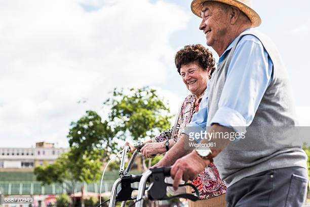 Happy senior couple with bicycle and wheeled walker