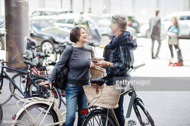 Happy senior couple with bicycles standing on city street