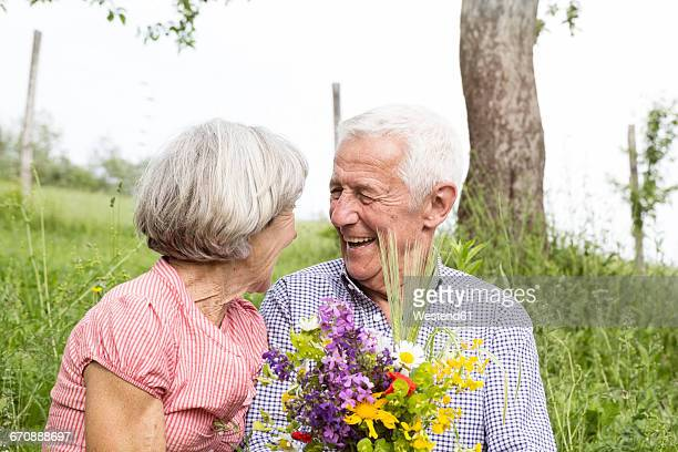 Happy senior couple with bunch of flowers outdoors