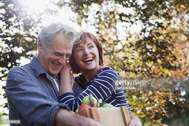 happy senior couple with bushel of apples hugging - 60 64 years stock pictures, royalty-free photos & images