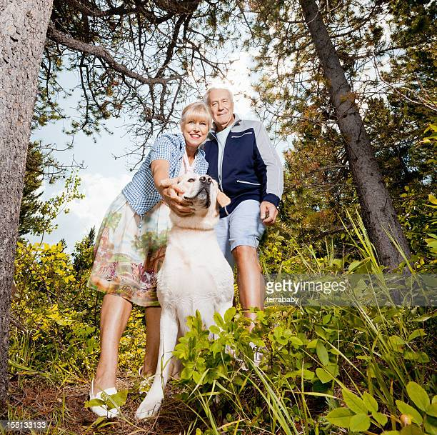 Happy Senior Couple with Dog in the Forest