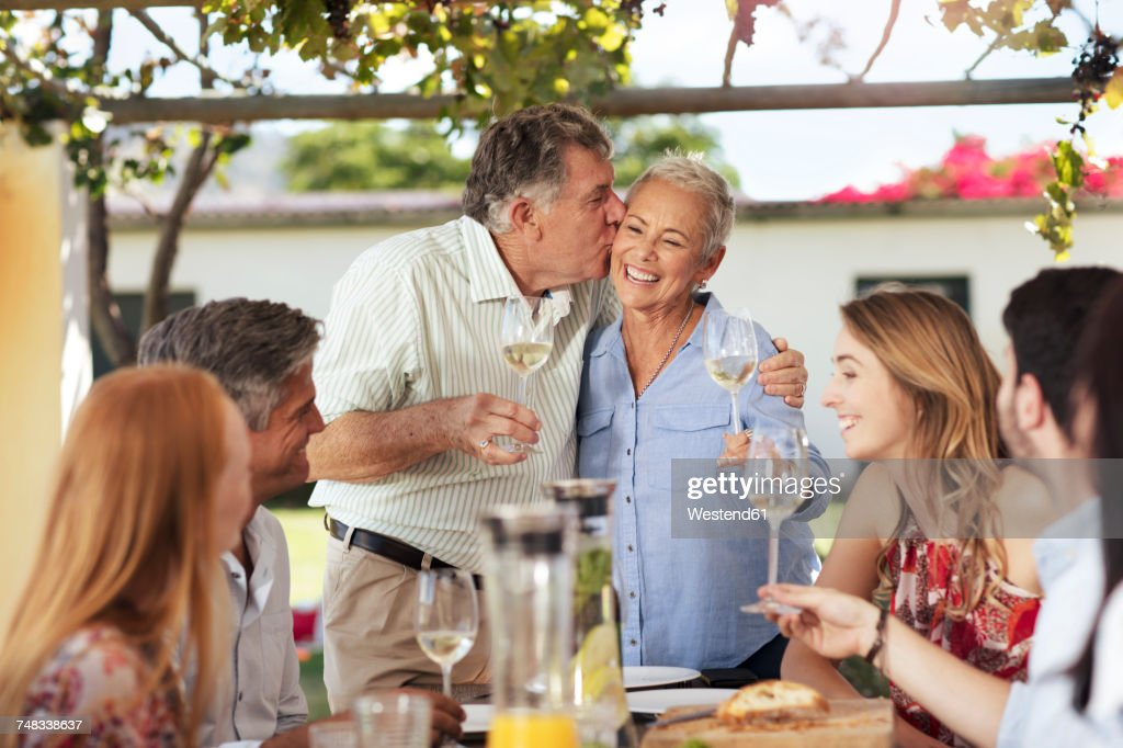 Happy senior couple with family having lunch together outside : Stock Photo