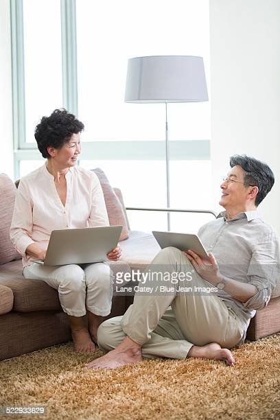 Happy senior couple with laptop and digital tablet