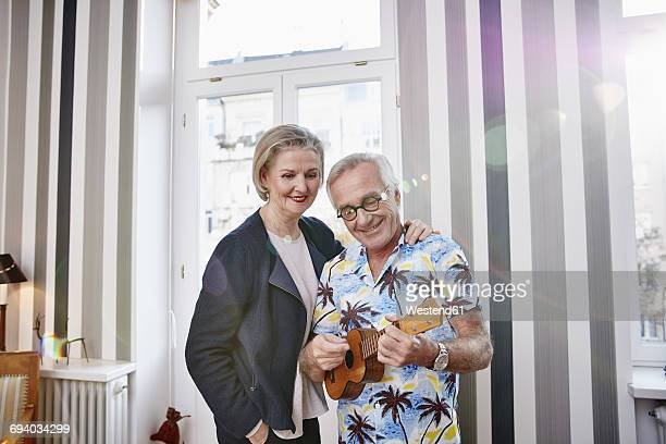 Happy senior couple with man in Hawaiian shirt playing ukulele