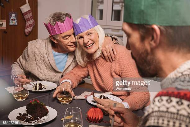 Happy senior couple with paper crowns having Christmas pudding
