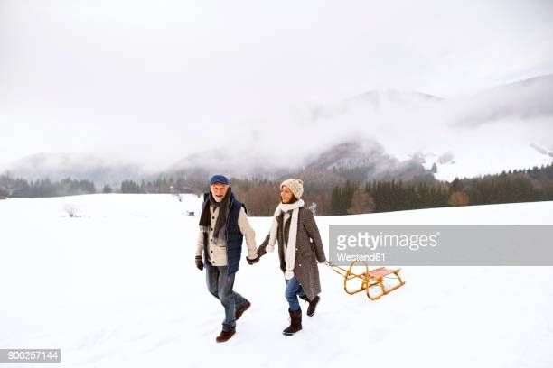 Happy senior couple with sledge walking in snow-covered landscape