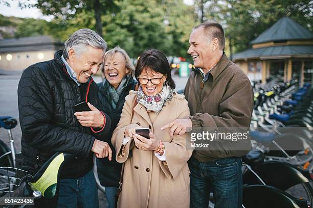 Happy senior couples using mobile phones at bicycle parking station