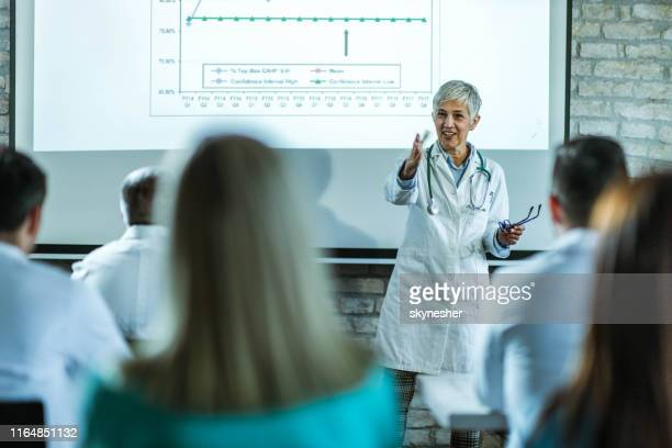 病院でプレゼンテーションをリードする幸せなシニア医師。 - 代表 ストックフォトと画像