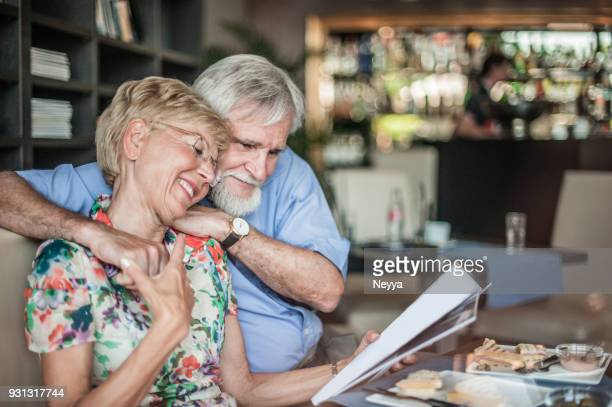 happy senior embracing couple reading a magazine in coffee bar, slovenia, europe - magazine stock pictures, royalty-free photos & images