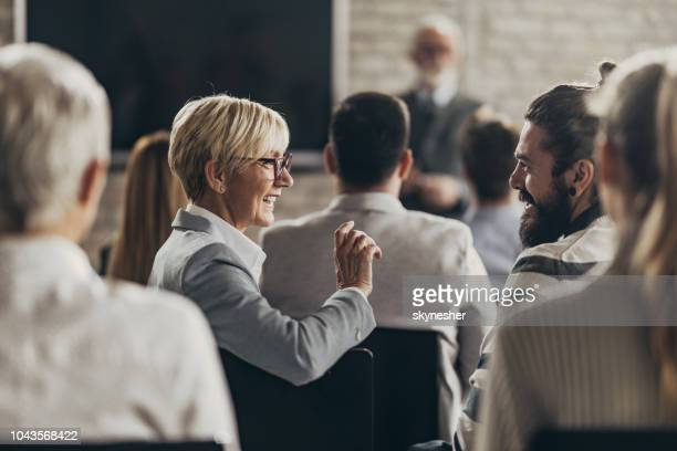 happy senior entrepreneur talking to her colleague on a seminar in a board room. - attending stock pictures, royalty-free photos & images