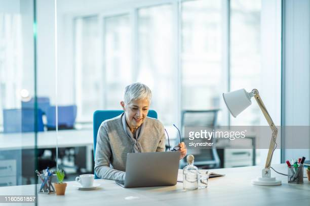 happy senior entrepreneur working on laptop in the office. - businesswear stock pictures, royalty-free photos & images