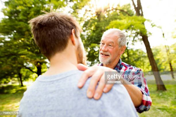 happy senior father and his adult son in a park - hand auf der schulter stock-fotos und bilder