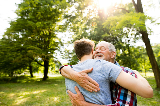 Happy senior father hugging his adult son in a park - gettyimageskorea