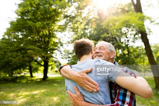 happy senior father hugging his adult son in a park - sohn stock-fotos und bilder