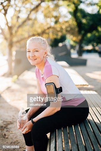Happy senior female runner rests after run