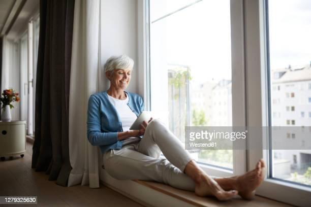 happy senior female using digital tablet while sitting on window at home - 60 64 años fotografías e imágenes de stock