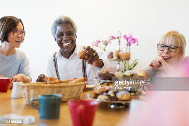 Happy senior friends enjoying afternoon tea desserts in community center