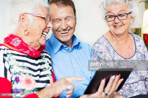 Happy senior friends using digital tablet at nursing home