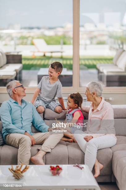 happy senior grandparents talking to their grandchildren and enjoying together at home. - penthouse girls stock pictures, royalty-free photos & images