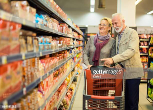 happy senior grocery grocery shopping. - spending money stock pictures, royalty-free photos & images